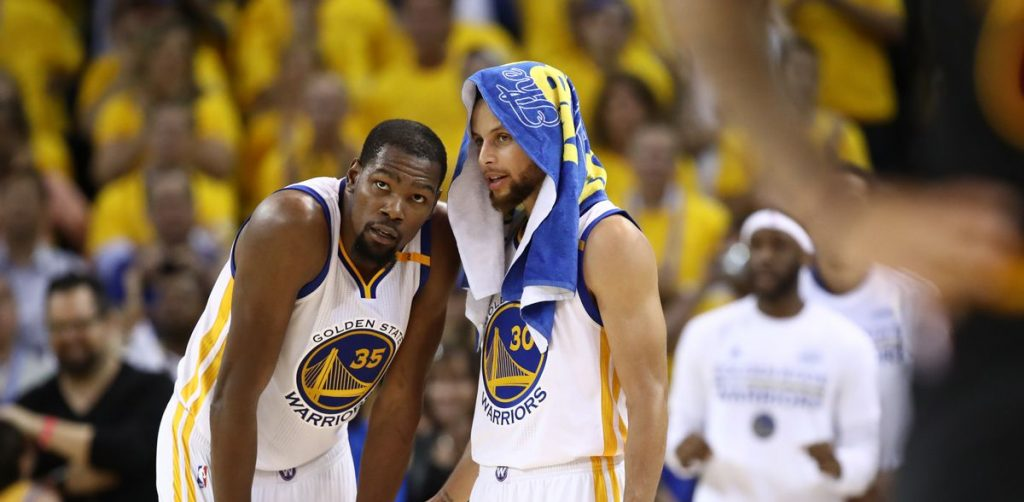 Kevin Durant et Stephen Curry discutent pendant un match des Warriors.