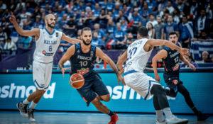 Evan Fournier devant deux joueurs Grecs, sous le maillot de l'équipe de France