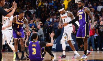 Les joueurs des Lakers Kentavious Caldwell-Pope et Lebron James relèvent leur coéquipier, Anthony Davis, lors du match opposant les Los Angeles Lakers aux Denver Nuggets, le 12 février 2020