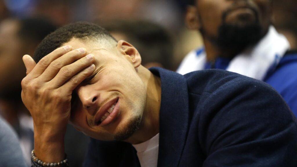 Stephen Curry cache ses yeux avec sa main, sur le banc des Golden State Warriors