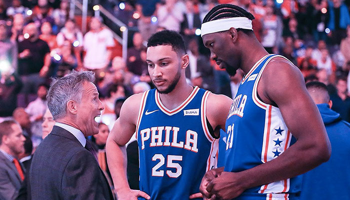 Brett Brown en discussion avec Ben Simmons et Joel Embiid lors d'un match des Phildelphia Sixers