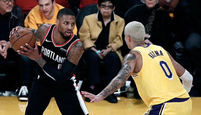 La superstar NBA Damian Lillard, ballon en main, face Kyle Kuzma lors d'un match entre les Portland Trail Blazers et les Los Angeles Lakers