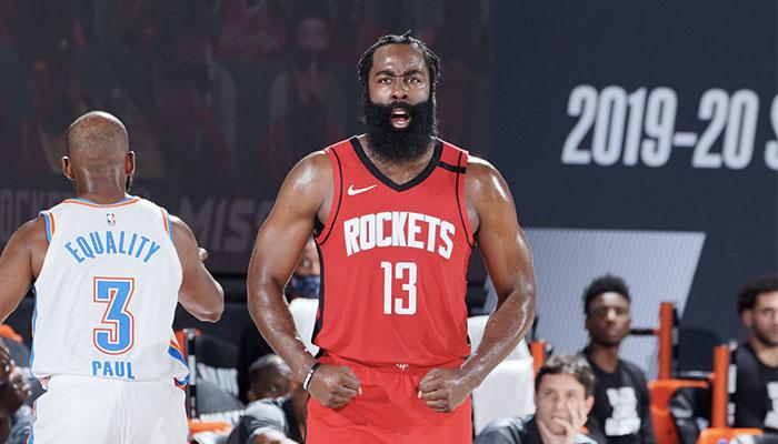 La superstar NBA James Harden montre les muscles devant Chris Paul lors d'un match de playoffs entre les Houston Rockets et le Oklahoma City Thunder