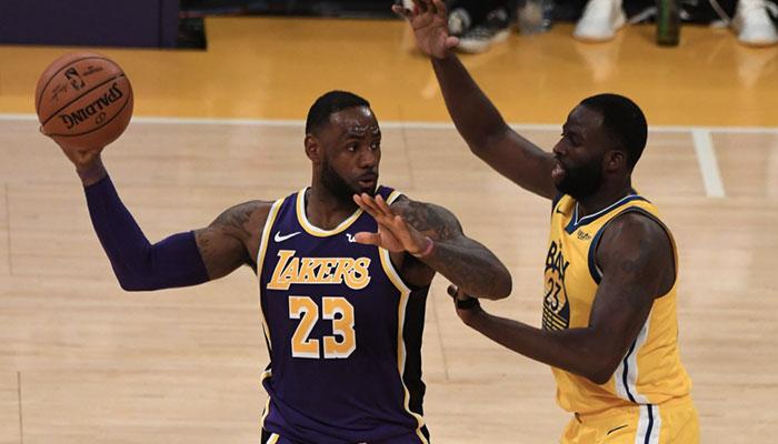 La superstar NBA des Los Angeles Lakers LeBron James, ballon en main, face à l'intérieur des Golden State Warriors Draymond Green