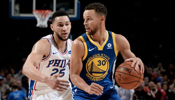 Les superstars NBA Ben Simmons et Stephen Curry, balle en main, en duel lors d'un match opposant les Philadelphia 76ers aux Golden State Warriors