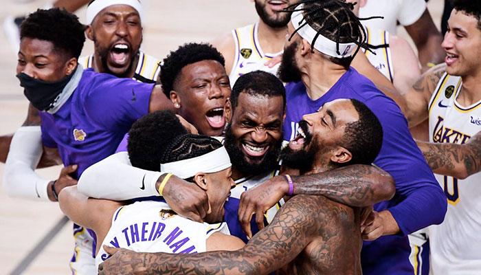 Les joueurs des Los Angeles Lakers Kostas Antetokounmpo, Kentavious Caldwell Pope, Quinn Cook, Devontae Cacok, LeBron James, JaVale McGee, J.R. Smith et Kyle Kuzma célèbrent le titre NBA