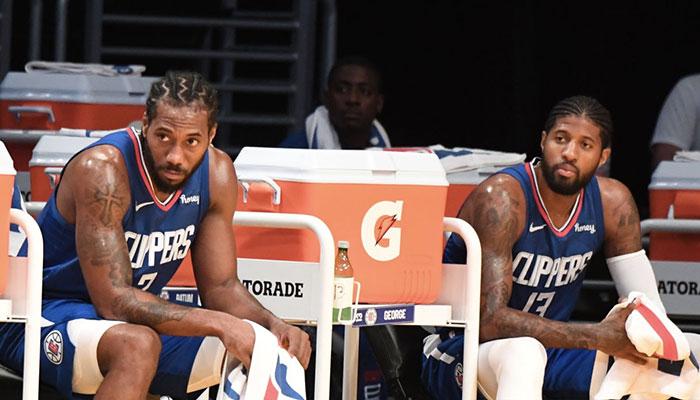 Les stars des Los Angeles Clippers, Kawhi Leonard (gauche) et Paul George (droite), sur le banc de leur équipe lors d'un match de pré-saison NBA face aux Los Angeles Lakers