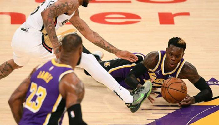 Dennis Schroder à la lutte avec le maillot des Lakers devant Lebron James