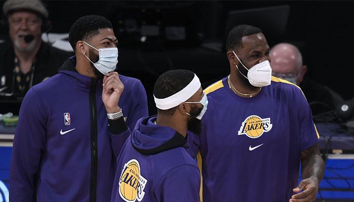 Anthony Davis, LeBron James et Markieff Morris tout sourire derrière leurs masques lors d'un match NBA des Los Angeles Lakers