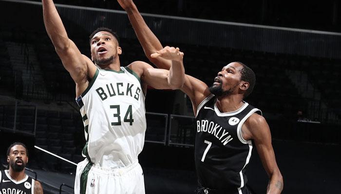 Les deux superstars NBA Giannis Antetokounmpo et Kevin Durant, à la lutte sous le panneau lors d'un match entre les Milwaukee Bucks et les Brooklyn Nets