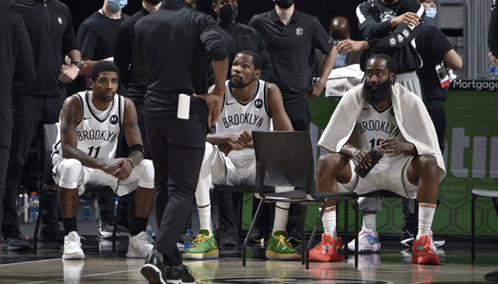 Les superstars NBA des Brooklyn Nets, Kyrie Irving, Kevin Durant et James Harden, assises lors d'un temps mort durant un match face aux Cleveland Cavaliers