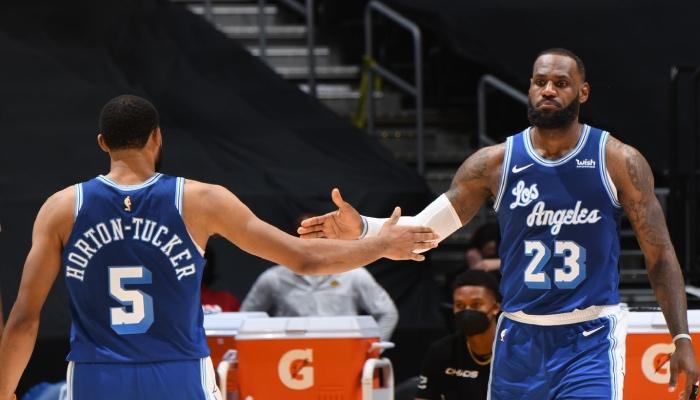 La superstar NBA des Los Angeles Lakers, LeBron James, tape dans la main de son jeune coéquipier, Talen Horton-Tucker, lors d'un match face aux Denver Nuggets