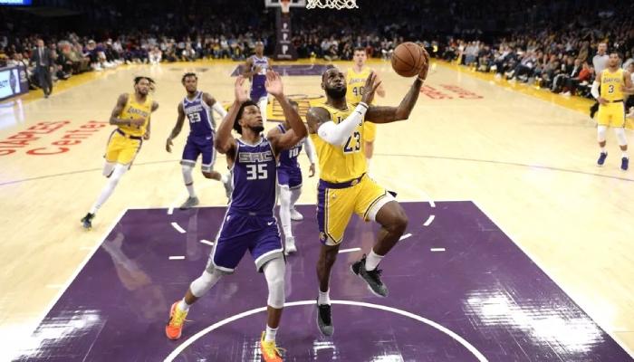 Le jeune intérieur NBA des Sacramento Kings, Marvin Bagley III, tente de contrer LeBron James lors d'un match face aux Los Angeles Lakers