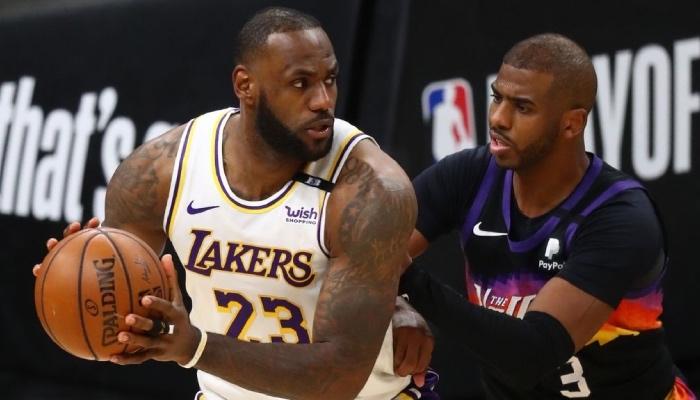 La superstar NBA des Los Angeles Lakers, LeBron James, ballon en main face au meneur vétéran des Phoenix Suns, Chris Paul