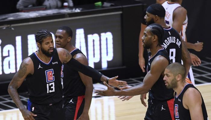Les joueurs NBA des Los Angeles Clippers, Paul George, Rajon Rondo, Marcus Morris, Kawhi Leonard et Nicolas Batum, rejoignent le banc de leur équipe lors d'un temps mort