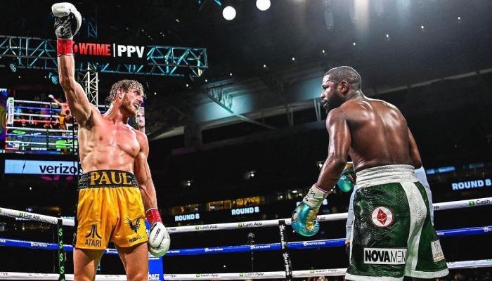 Le YouTubeur américain Logan Paul, lève le poing devant la légende de la boxe, Floyd Mayweather, durant le combat opposant les deux hommes