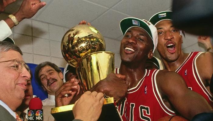 La légende NBA des Chicago Bulls, Michael Jordan, porte le trophée Larry O'Brien devant les yeux de Jerry Krause, Phil Jackson et Scottie Pippen